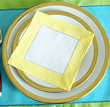 Festive colored trimmed cocktail napkin. Yellow color
